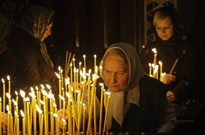Mourners light candles for the departed at Moscow's Cathedral of Christ the Saviour.