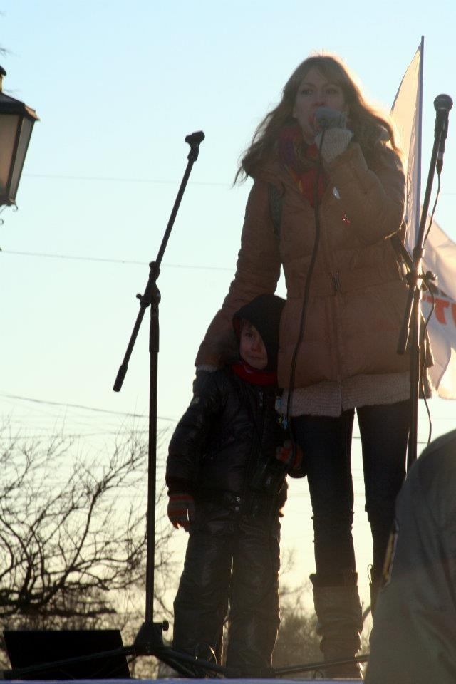 (Maria addresses a protest rally with son at her side.)