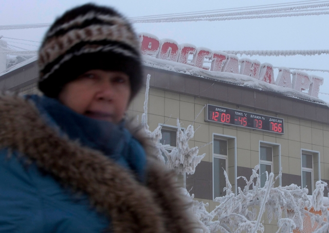 A woman passes a board on a building, displaying the local time, temperature, humidity and air pressure in Yakutsk. (photo: Maxim Shemetov, Reuters)